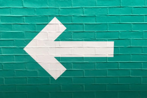 White arrow facing left on a turquoise brick wall